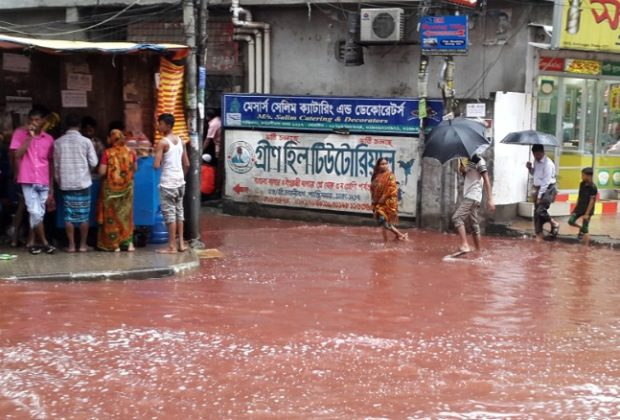People wade past a road turned red after blood from sacrificial animals on Eid al-Adha mixed with water from heavy rainfall in Dhaka, Bangladesh.