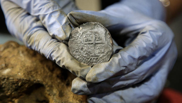 In this Wednesday, Sept. 21, 2016 photo, archaeologist Marie Kesten Zahn, of Yarmouth, Mass. displays a silver coin recovered from the wreckage of the pirate ship Whydah Gally at the Whydah Pirate Museum, in Yarmouth. STEVEN SENNE, AP